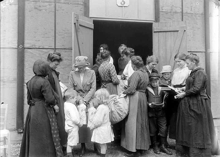 Entrepôt n°3 du CARD pendant la retraite de 1918 : Sue K. Watson de Virginie Occidentale avec des réfugiés, distribution de jouets et de livres
