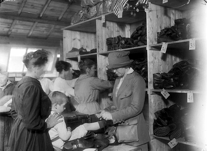 Adaptation des chaussures aux petits garçons à l'entrepôt, Madame Sue K. Watson de Virginie Occidentale, travailleuse au CARD