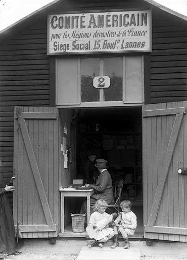 Entrepôt n°2 du Comité Américain : Mme Stockley, travailleuse au CARD, enfants avec des jouets assis à l'entrée