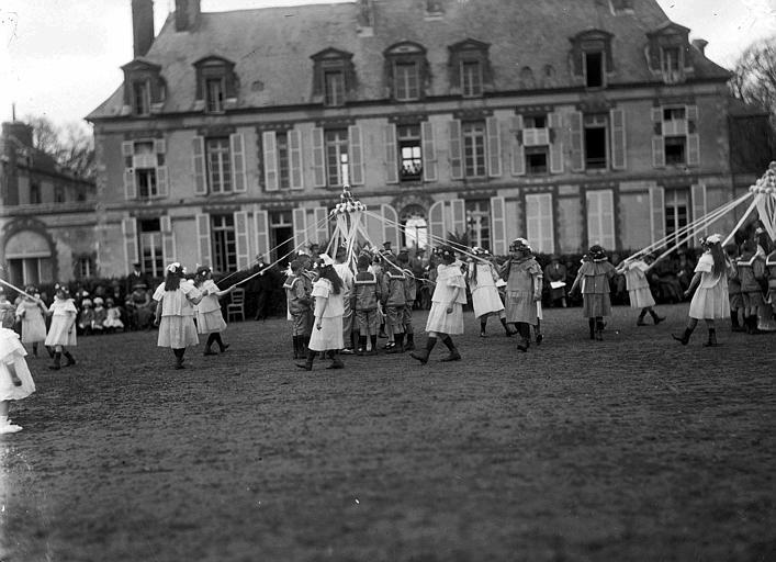 Parc, devant la façade du château, fête du 1er mai : 'Le Mai', danse autour de mâts de cocagne