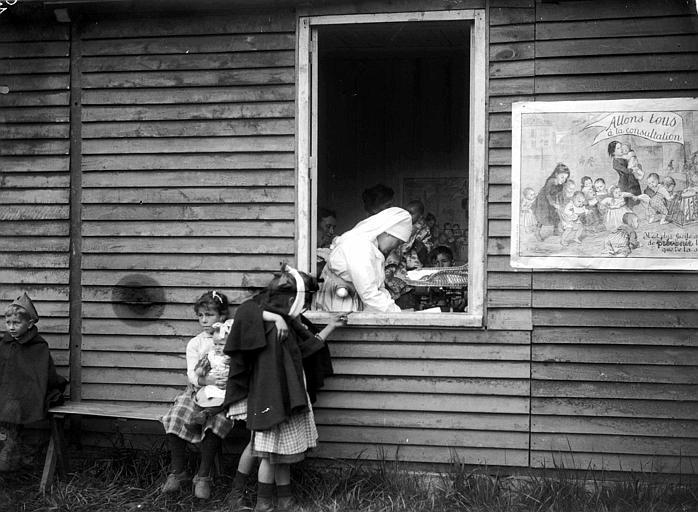Dispensaire du Comité Américain : Mlle Breckenridge en consultation pédiatrique vue au travers de la fenêtre