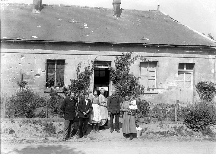 Famille posant devant la façade criblée d'impacts de sa maison