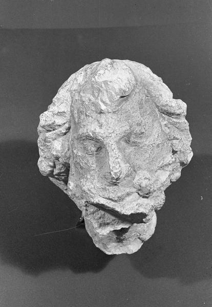 Statue en pierre de Romain, fragment : tête d'homme (très abîmée), de face