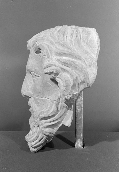 Statue en pierre de Romain, fragment : tête d'homme barbu (cassée en deux), profil gauche