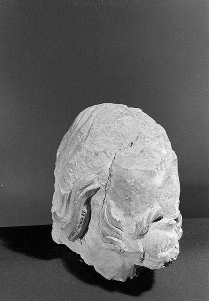 Statue en pierre de Courville, fragment : tête d'homme barbu, sans visage, de trois quarts droit