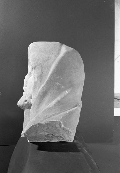 Statue en marbre blanc, fragment : tête de vieillard portant un capuchon, profil gauche