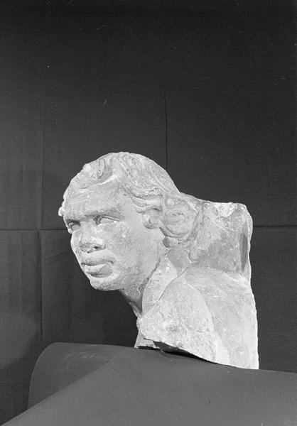 Statue en pierre de Romain, fragment : tête de bourreau imberbe provenant du portail nord de la façade ouest, de trois quarts gauche