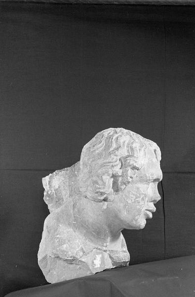 Statue en pierre de Romain, fragment : tête de bourreau imberbe provenant du portail nord de la façade ouest, de trois quarts droit