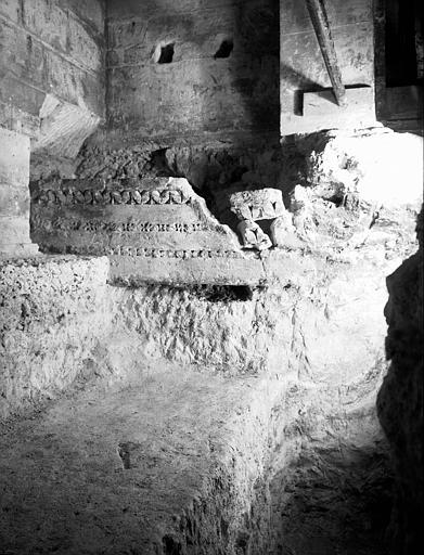 Crypte carolingienne : sarcophage formé d'éléments romains encastrés dans l'angle nord-ouest, vu depuis le puits, décor latéral