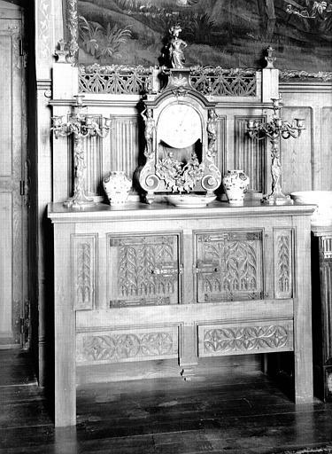 Bahut crédence en bois du 15e siècle et garniture de cheminée constituée d'une pendule Louis XIV et de candélabres Louis XV, situés dans le Grand Salon
