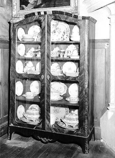 Armoire à portes vitrées Louis XV contenant des pièces de porcelaine, située dans le Grand Salon