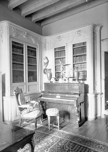 Bibliothèque d'angle en bois sculpté et peint Louis XV, située dans le Petit Salon