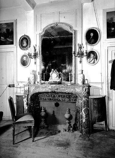 Glace avec cadre en bois doré fin Louis XV, petite pendule en bronze et marbre Louis XVI, situés dans la Chambre Rouge