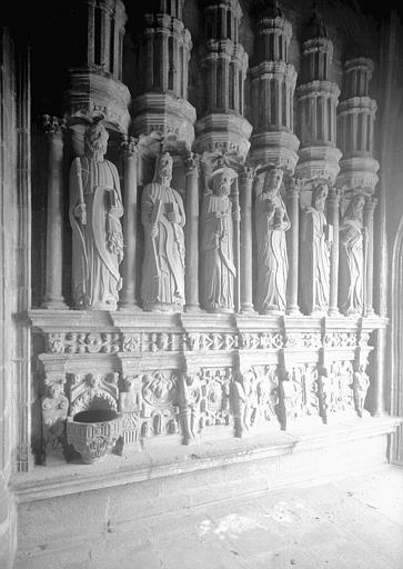Décoration latérale du porche : les statues des apôtres et un bénitier en granit dans la prise de vue