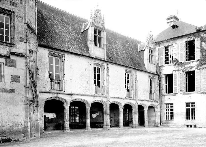 Cour intérieure : bâtiments à galerie à gauche de l'entrée et bâtiment du fond de la cour