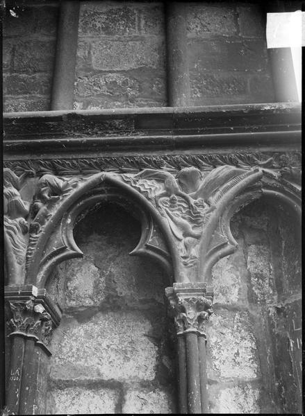 Portail central de la façade ouest, détail du soubassement avec ogives trilobées et scènes historiées