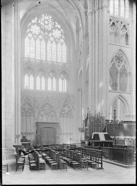 Intérieur : transept nord avec vitraux depuis le transept sud, avec en partie haute une baie à quatre lancettes surmontées par trois oculi