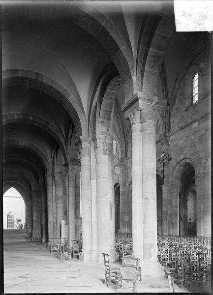 Intérieur : bas-côté sud vers l'entrée, avec colonnes à chapiteaux sculptés