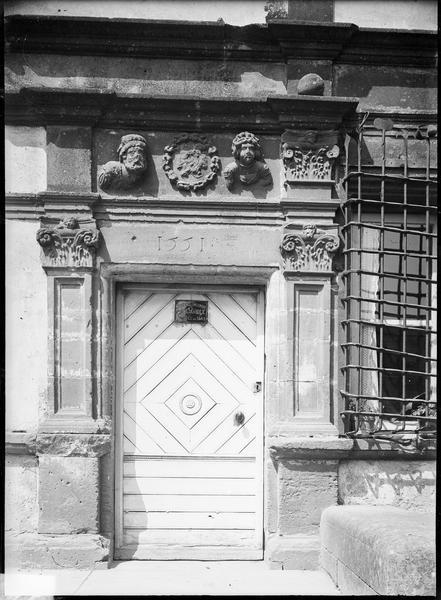 Porte encadrée de colonnes à chapiteaux corinthiens et surmontée de deux têtes sculptées