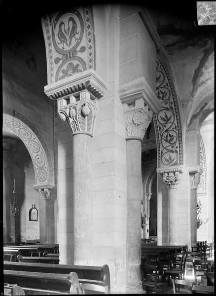 Intérieur : colonnes à chapiteaux sculptés et arcades peintes du bas-côté sud vers la nef