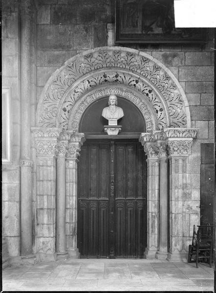 Intérieur : déambulatoire, porte romane surmontée d'un buste du Cardinal de la Luzerne