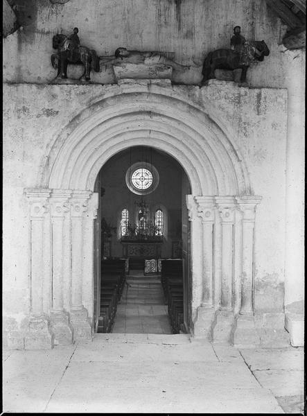 Intérieur : nef et vitraux du choeur depuis le porche fermé avec portail surmonté de sculptures représentant le marthyr de Saint-Hippolyte