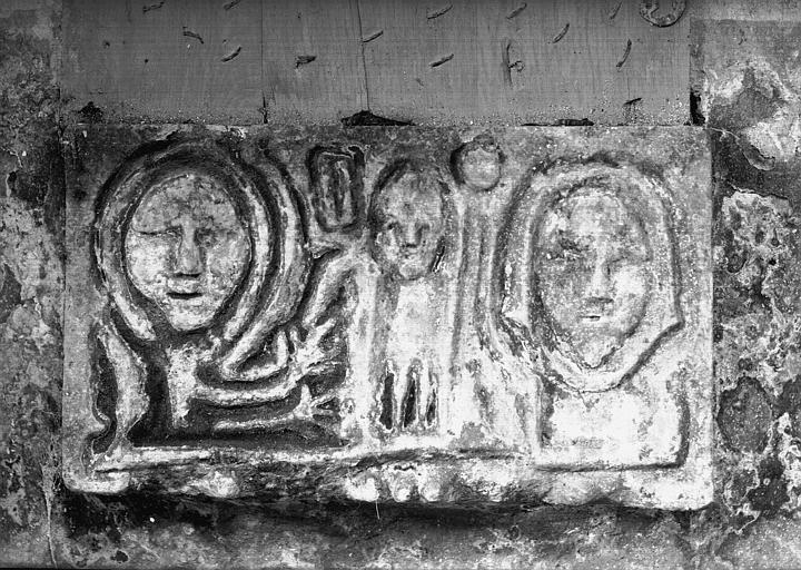 Dalle en pierre sculptée à visages humains