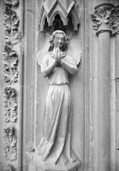 Portail central de la façade ouest, première voussure gauche, première rangée : ange en prière, de face