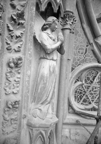 Portail central de la façade ouest, première voussure gauche, première rangée : ange en prière, de trois quarts droit