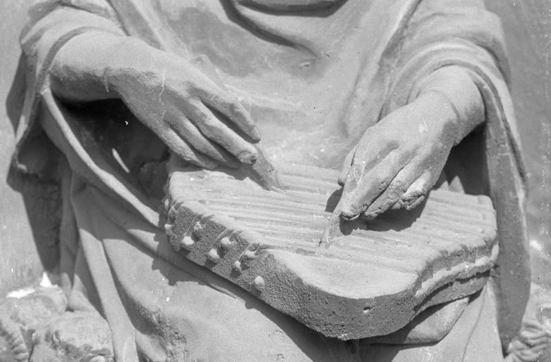 Portail central de la façade ouest, première voussure gauche, deuxième rangée : roi assis jouant du psaltérion, détail des mains sur l'instrument