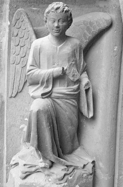 Portail central de la façade ouest, première voussure gauche, quatrième rangée : ange agenouillé, de face
