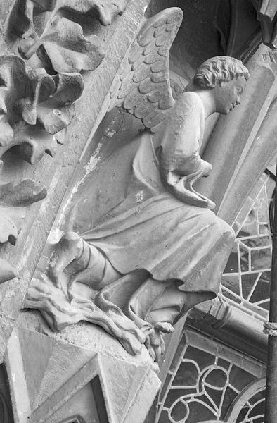 Portail central de la façade ouest, première voussure gauche, quatrième rangée : ange agenouillé, profil droit