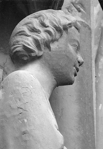 Portail central de la façade ouest, première voussure gauche, quatrième rangée : ange agenouillé, détail de la tête, profil droit
