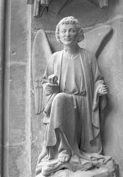Portail central de la façade ouest, première voussure gauche, cinquième rangée : ange agenouillé, de face