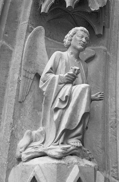 Portail central de la façade ouest, première voussure gauche, cinquième rangée : ange agenouillé, de trois quarts droit