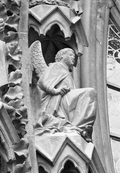 Portail central de la façade ouest, première voussure gauche, sixième rangée : ange agenouillé, de trois quarts droit dessous