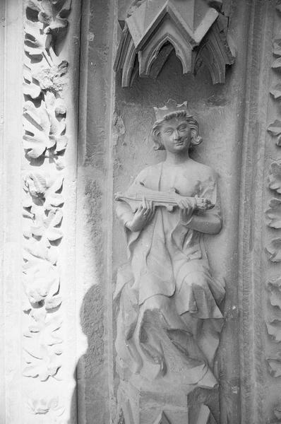 Portail central de la façade ouest, deuxième voussure gauche, deuxième rangée : roi assis jouant de la guiterne, de face