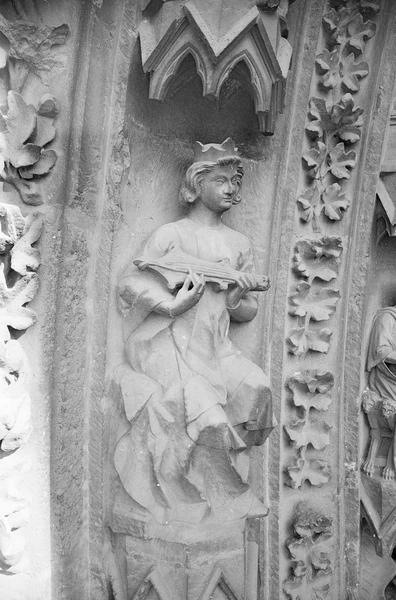 Portail central de la façade ouest, deuxième voussure gauche, deuxième rangée : roi assis jouant de la guiterne, de trois quarts droit