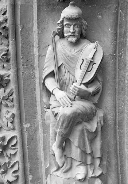 Portail central de la façade ouest, deuxième voussure gauche, troisième rangée : homme assis tenant une vielle et un archet, de face