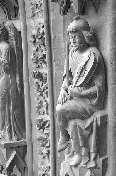 Portail central de la façade ouest, deuxième voussure gauche, troisième rangée : homme assis tenant une vielle et un archet, de trois quarts gauche