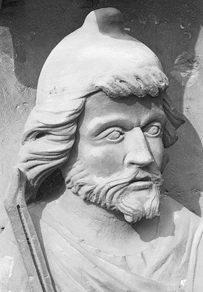 Portail central de la façade ouest, deuxième voussure gauche, troisième rangée : homme assis tenant une vielle et un archet, détail de la tête de trois quarts droit