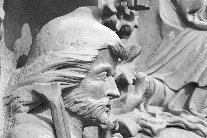 Portail central de la façade ouest, deuxième voussure gauche, troisième rangée : homme assis tenant une vielle et un archet, détail de la tête, profil droit