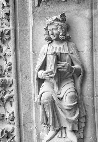 Portail central de la façade ouest, deuxième voussure gauche, quatrième rangée : homme assis jouant de la harpe, de face