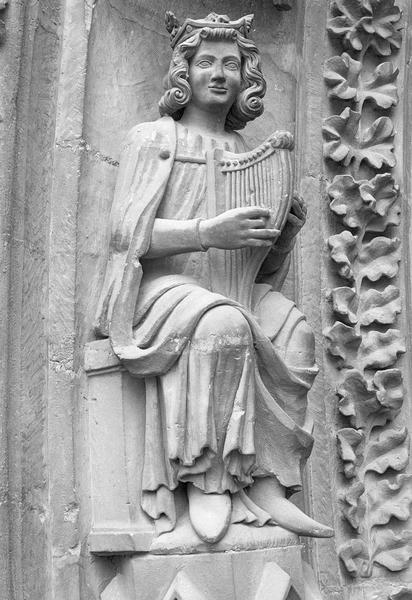 Portail central de la façade ouest, deuxième voussure gauche, quatrième rangée : homme assis jouant de la harpe, de trois quarts droit