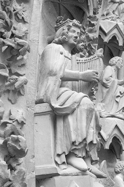 Portail central de la façade ouest, deuxième voussure gauche, quatrième rangée : homme assis jouant de la harpe, profil droit du dessous