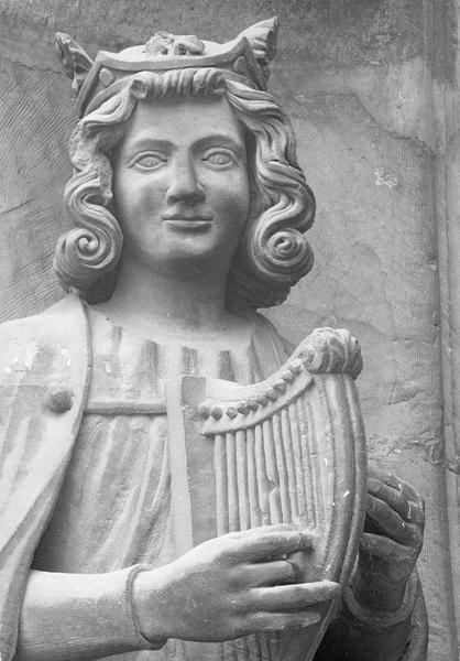 Portail central de la façade ouest, deuxième voussure gauche, quatrième rangée : homme assis jouant de la harpe, détail du buste de face