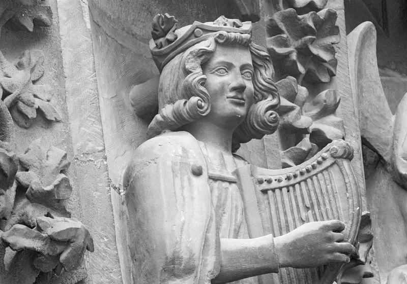 Portail central de la façade ouest, deuxième voussure gauche, quatrième rangée : homme assis jouant de la harpe, détail du buste de trois quarts droit