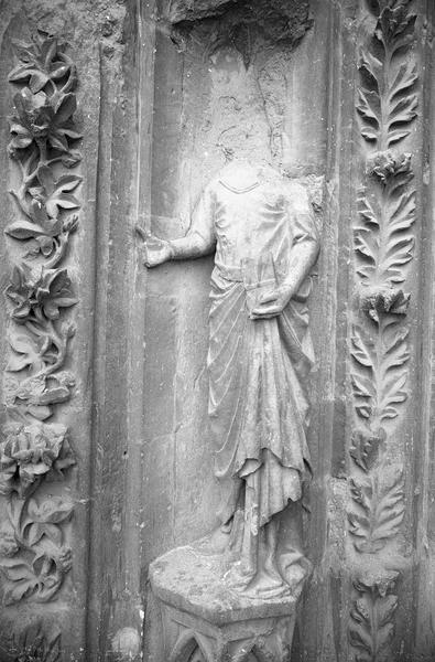 Portail central de la façade ouest, quatrième voussure gauche, première rangée : personnage acéphale tenant un livre, de face