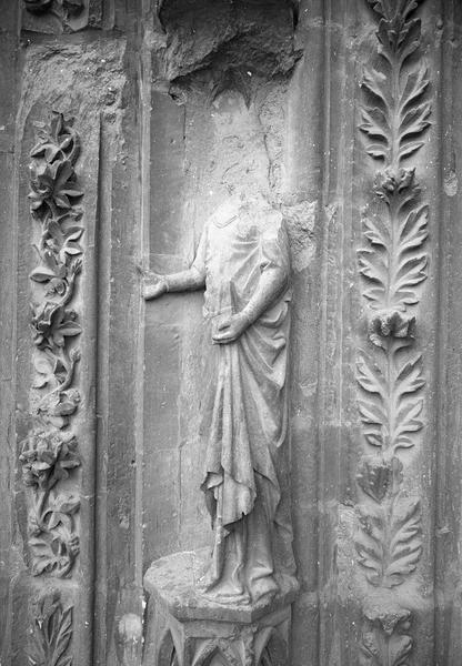 Portail central de la façade ouest, quatrième voussure gauche, première rangée : personnage acéphale tenant un livre, de trois quarts gauche