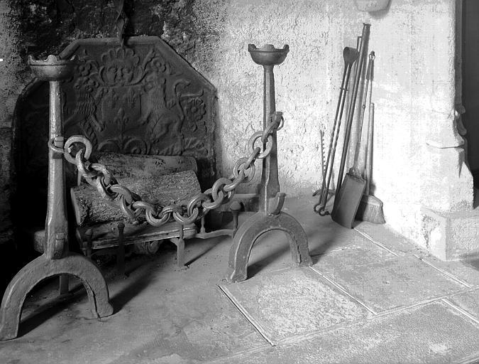 Taque de cheminée à crémaillère en fonte et paire de chenêts avec  chaines en fer forgé, situés dans la grande salle du  rez-de-chaussée